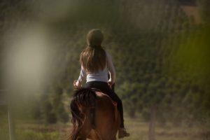 Jeune femme à cheval vue de dos, écartant légèrement sa main gauche de l'axe de son corps